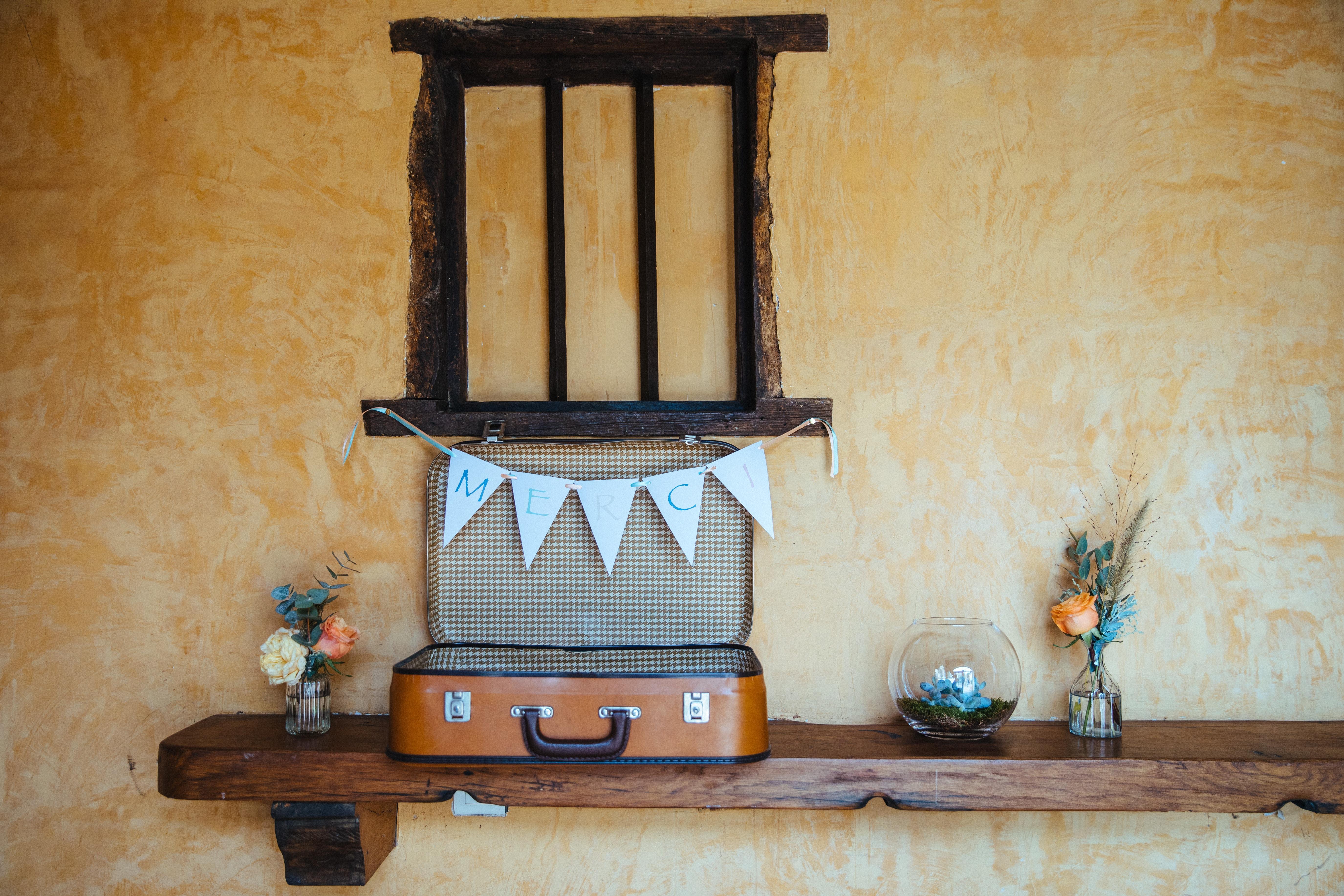 décoration de mariage orange - livre d'or - urne - valise ancienne - guirlande de fanions